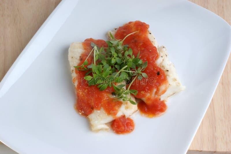 Gekookte kabeljauwlendestukken met tomatensaus stock afbeelding