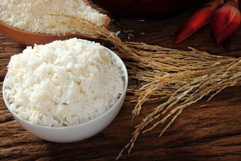 Gekookte rijst, ongekookte rijst en padie op houten lijst royalty-vrije stock fotografie