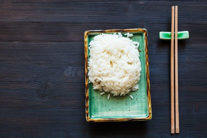 Gekookte rijst op groene plaat en eetstokjes op rust stock foto's