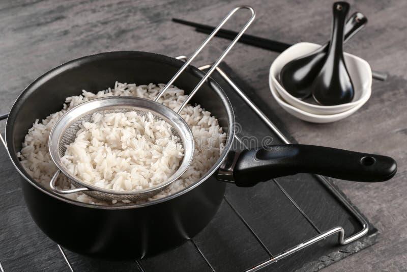 Gekookte rijst in steelpan met zeefje stock fotografie