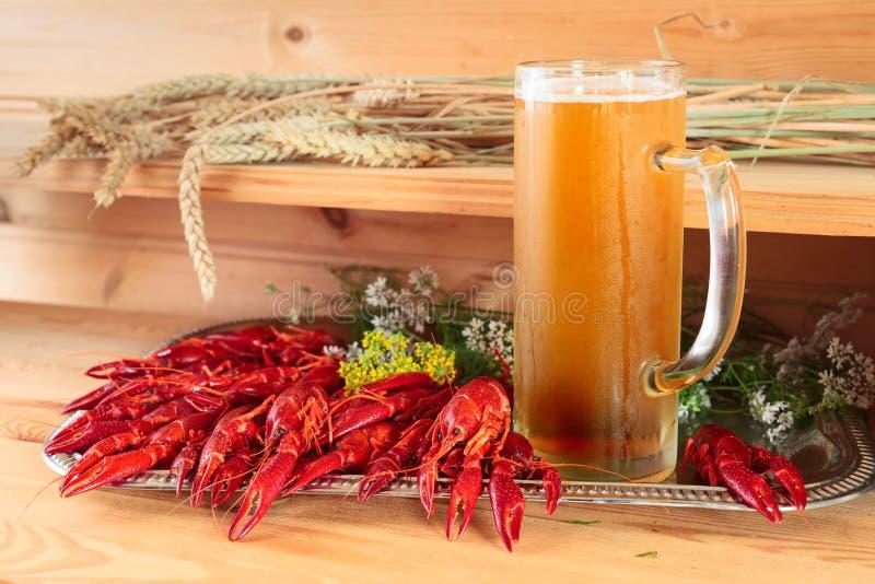 Gekookte rivierkreeften en mok met bier stock foto's