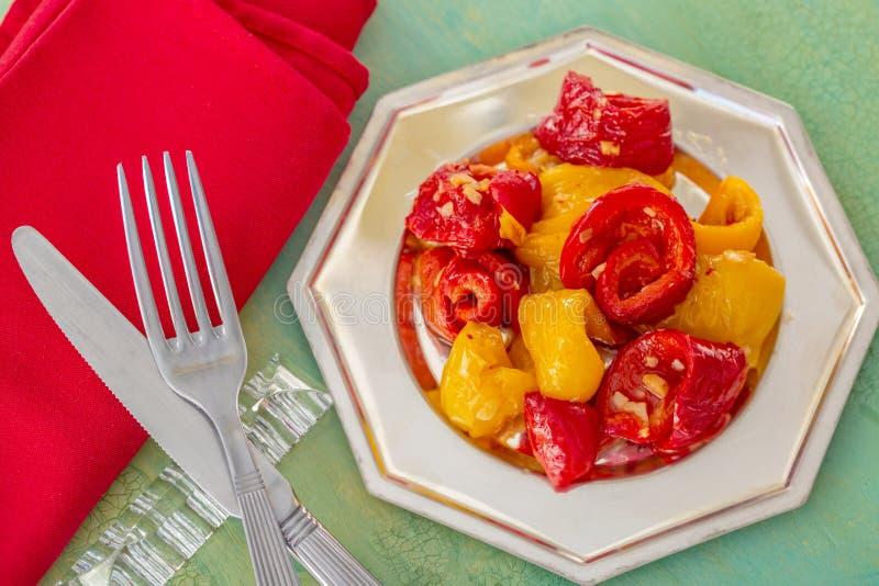 Gekookte rode gele gebraden paprika's op een verzilverd tafelgerei r Oude lijst royalty-vrije stock afbeelding