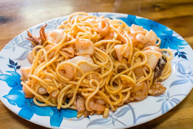 Gekookte spaghetti met gebraden zeevruchten op plaat met ornament stock afbeelding