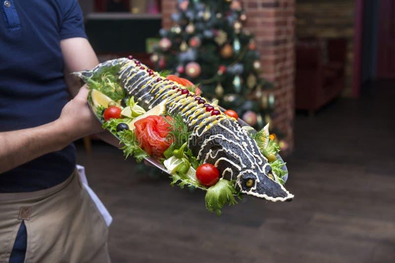 Gekookte steur op een dienblad in de handen van een kelner, visschotel royalty-vrije stock afbeeldingen