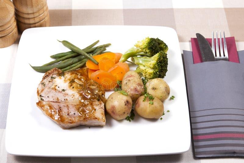Gekookte varkensvleeslapje vlees en groenten stock afbeelding