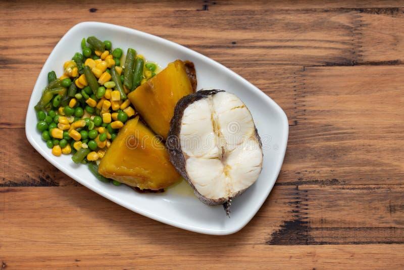 Gekookte vissen met groenten op witte schotel stock afbeelding