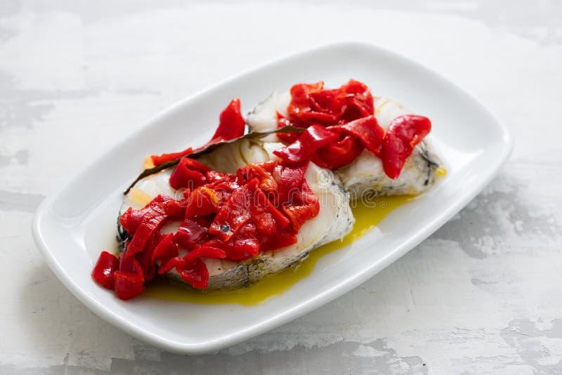 Gekookte vissen met Spaanse peper en olijfolie op witte schotel stock fotografie