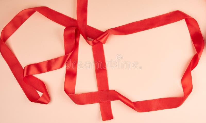 gekräuseltes rotes Satinband auf einem beige Hintergrund lizenzfreie stockfotografie