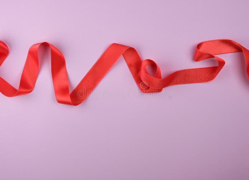 gekräuseltes rotes Satinband auf einem purpurroten Hintergrund stockfotos