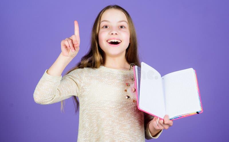 Gekregen groot idee Gelukkig meisje die open ideeboek houden en vinger opgeheven houden Glimlachend klein kind die een idee hebbe royalty-vrije stock foto