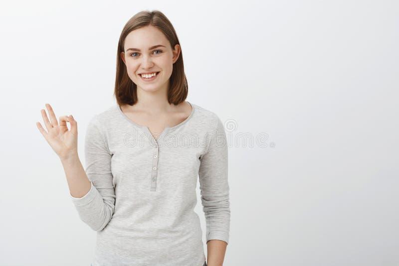 Gekregen het, o.k. Vriendschappelijke gelukkige en creatieve jonge vrouw met kort bruin kapsel die o.k. of perfect teken met opge royalty-vrije stock fotografie