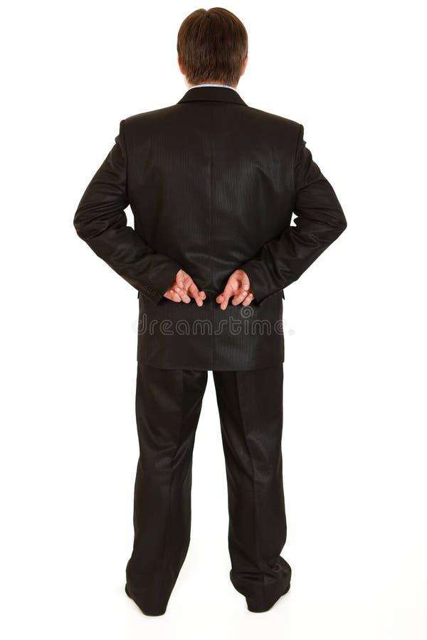 Gekreuzte Finger des Geschäftsmannes Holding nach zurück stockbild