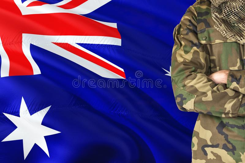 Gekreuzter Armsoldat mit nationaler wellenartig bewegender Flagge auf Hintergrund - Militärthema XXX stockfotos