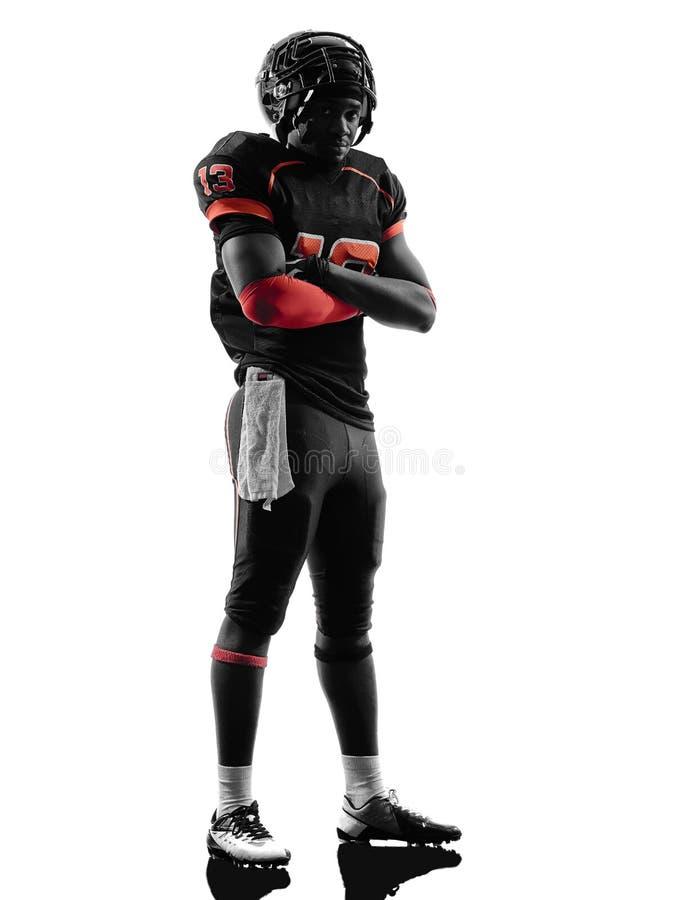 Gekreuztes Schattenbild des Spielers des amerikanischen Fußballs stehende Arme stockfoto