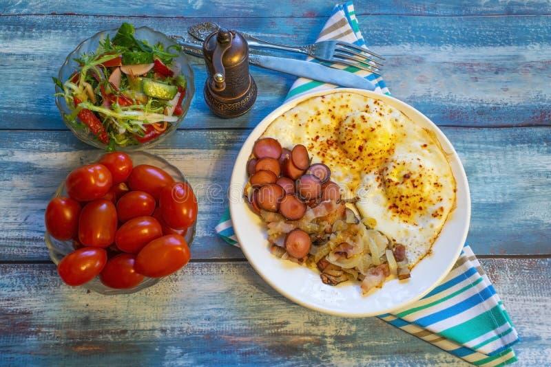 Gekrochene Eier mit Speck, Zwiebel und Wurst lizenzfreie stockfotografie