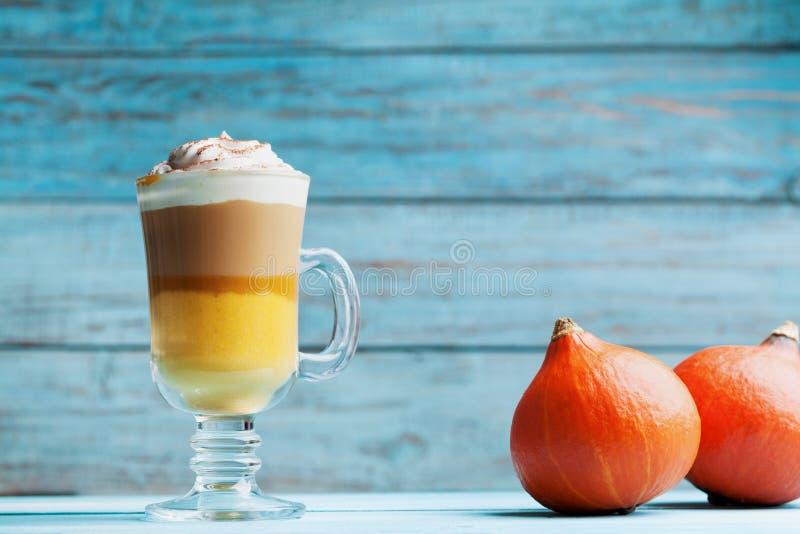 Gekruide pompoen latte of koffie in glas op turkooise houten lijst De herfst, dalings of de winter hete drank stock afbeelding