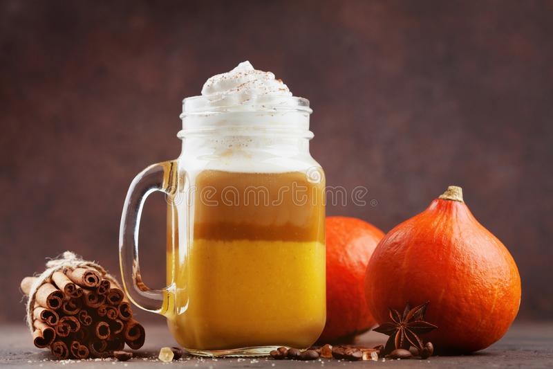 Gekruide pompoen latte of koffie in glaskruik op bruine achtergrond De herfst, dalings of de winter hete drank royalty-vrije stock foto