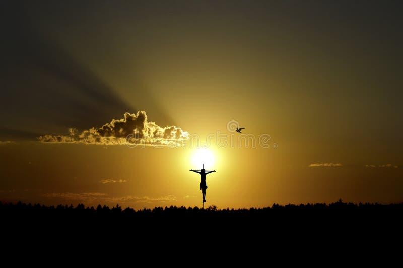 Gekruisigd op het kruis tegen de achtergrond van de het plaatsen zon stock fotografie