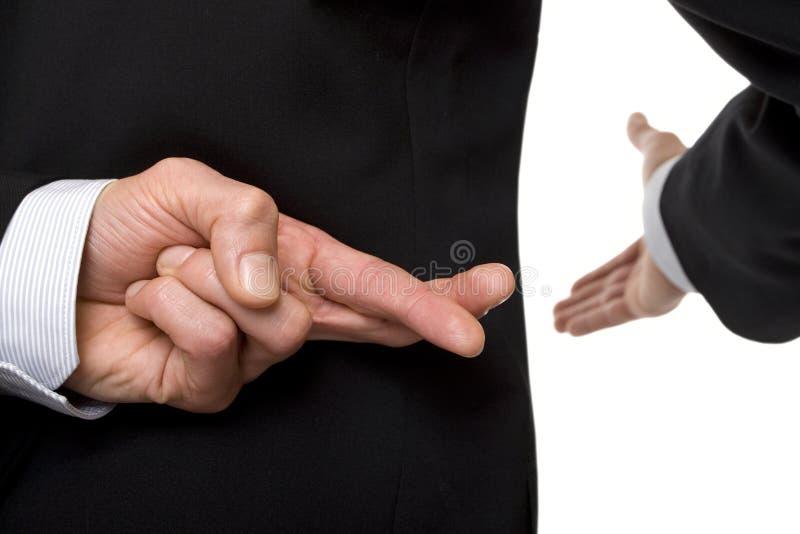 Gekruiste vingers bij handdruk stock fotografie