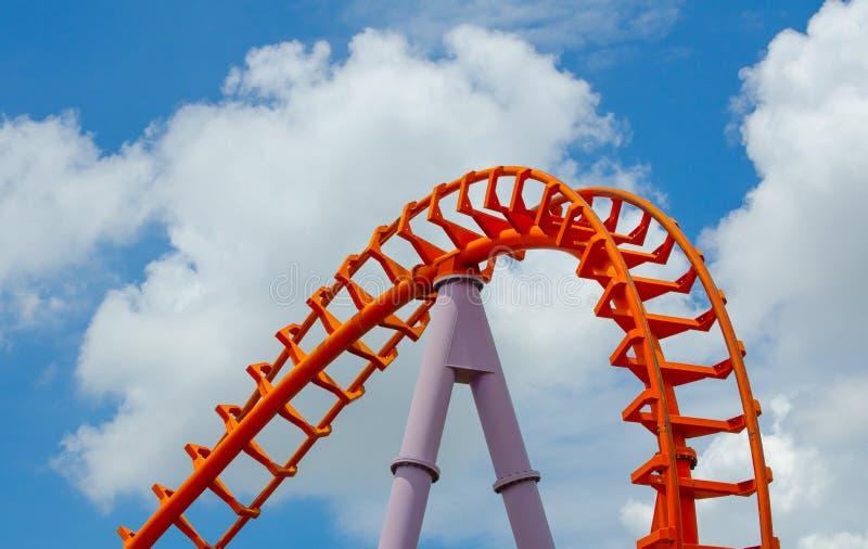 Gekurvt von der orange Achterbahnbahn im Abschluss oben lokalisiert auf bewölktem Hintergrund des blauen Himmels stockfotos