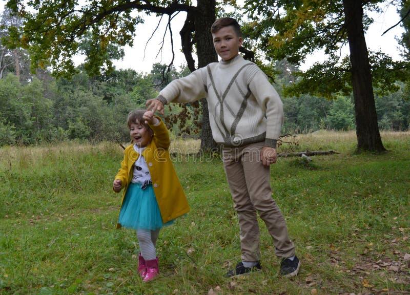 Gelächterspaßschwesterbruder-Vatiliebe außerhalb des Waldjungen lächelnder Wegnatur draußen f des jungen des Sommers Tochterpaarb lizenzfreie stockfotografie