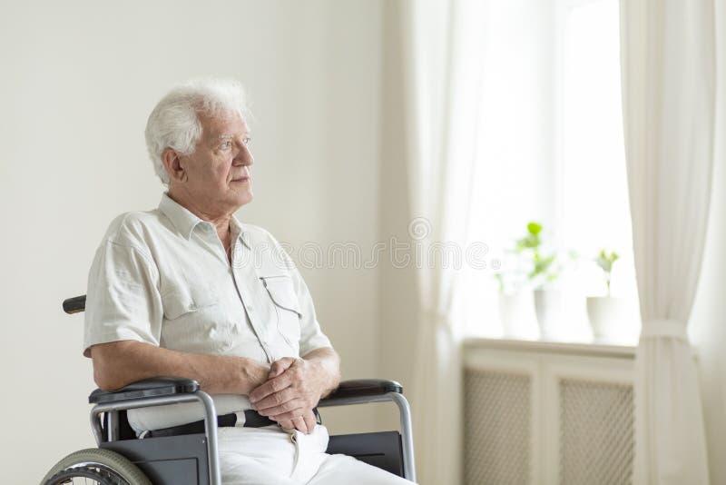 Gelähmter, älterer Mann in einem Rollstuhl allein in einem Raum lizenzfreies stockfoto