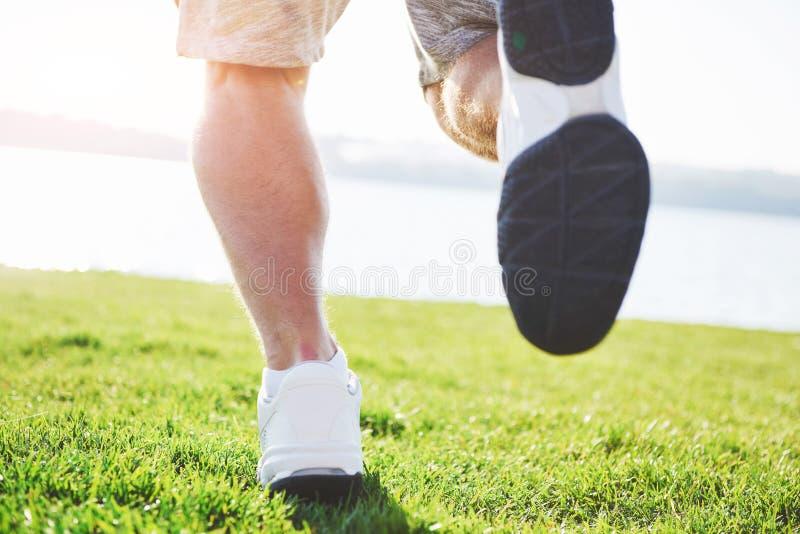 Geländelauf im Freien im Sommersonnenscheinkonzept für das Trainieren, Eignung und gesunden Lebensstil Schließen Sie oben von den stockfotografie