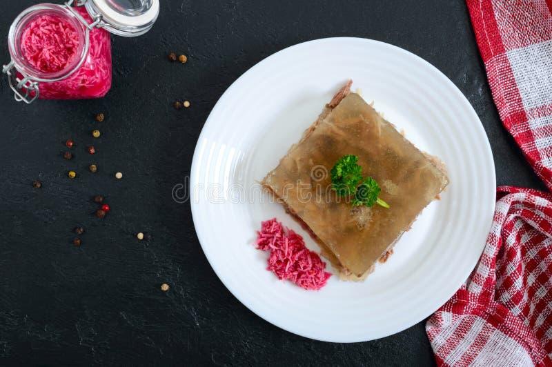 Gel?e de viande avec le raifort ?pic? d'un plat blanc sur un fond noir Plat froid traditionnel slave image libre de droits