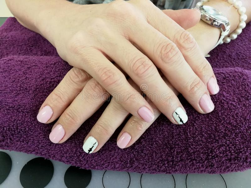 Soft pink. Gel soft pink nails with free hand stripe and hart nail art stock images