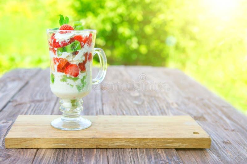 gelaagd dessert met aardbeien en roomkaas op houten lijst over groene tuinachtergrond royalty-vrije stock afbeeldingen