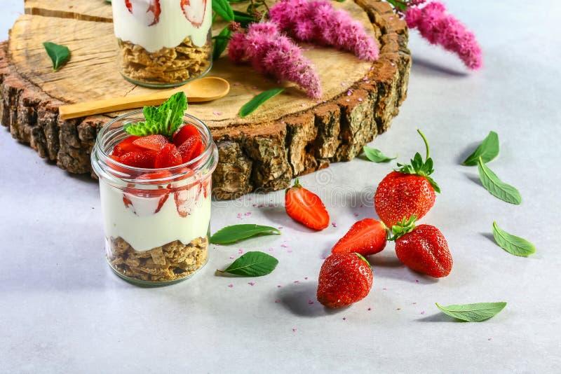 Gelaagd dessert met aardbeien, koekjescake en roomkaas op een witte houten achtergrond Selectieve nadruk stock foto's