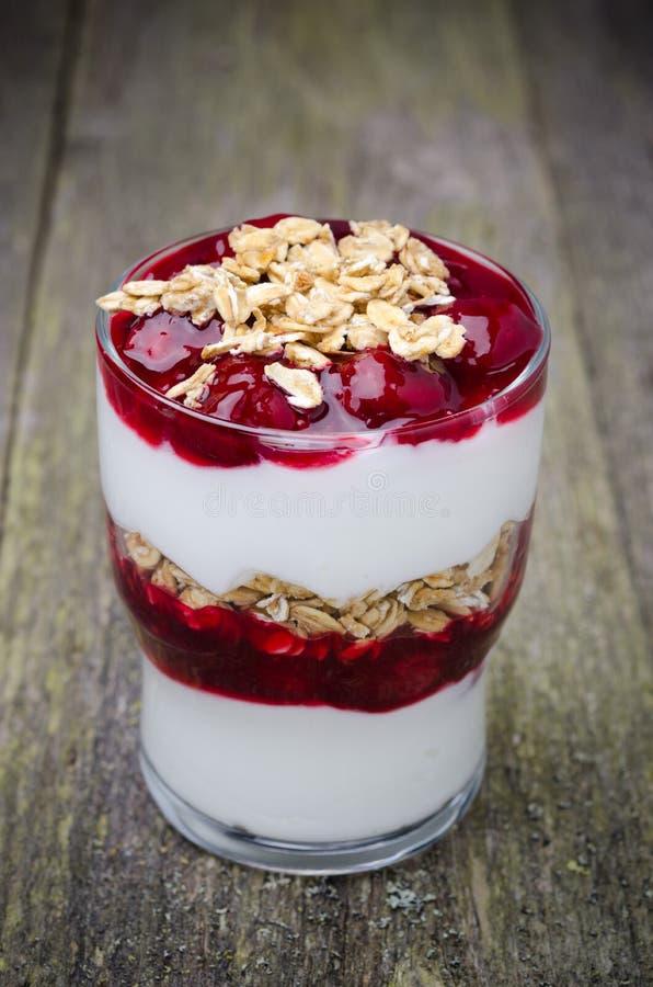 Gelaagd dessert met yoghurt, kersen en granola stock foto's