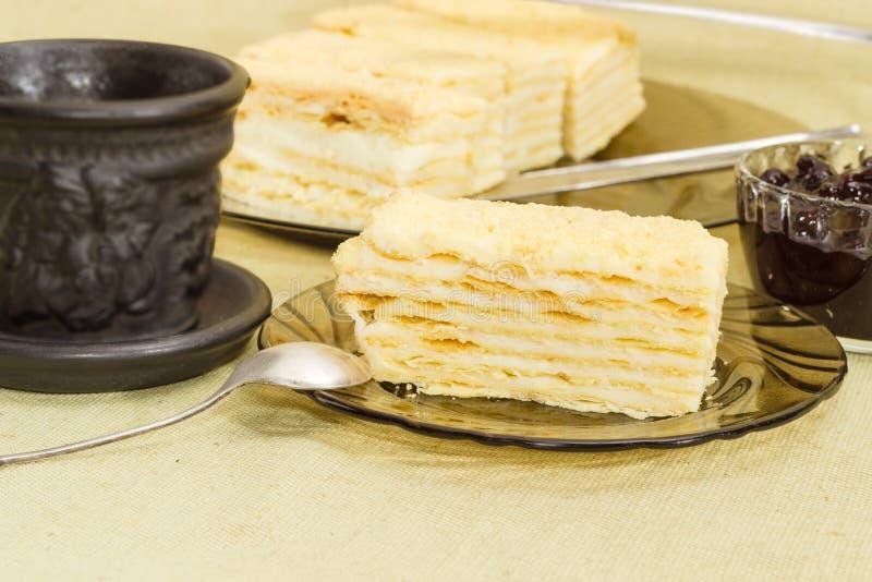 Gelaagde cake op achtergrond van rest van cake, kop, jam stock fotografie