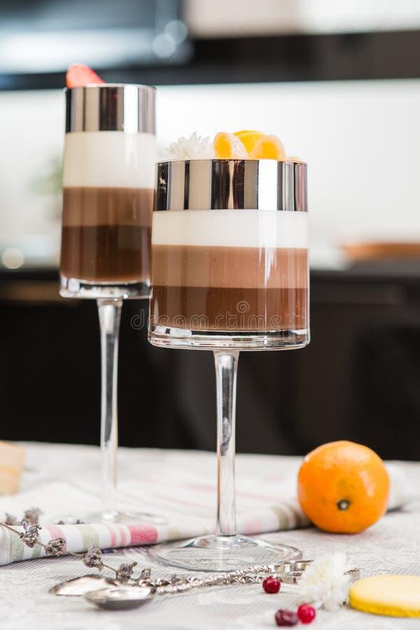 Gelaagde chocoladedesserts in glazen Plakken van mandarine op een bovenkant van snoepje Selectieve nadruk royalty-vrije stock fotografie