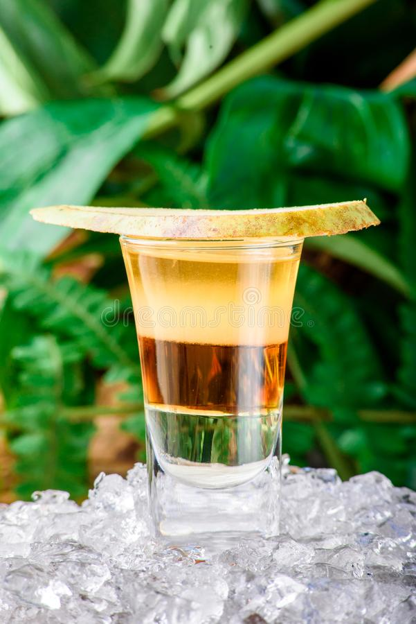 Gelaagde gele geschotene die cocktail met perenplak wordt verfraaid op ijs Geïsoleerdc op groene achtergrond royalty-vrije stock afbeelding