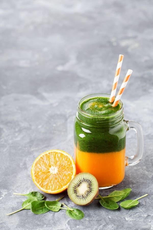 Gelaagde gezonde smoothie met spinazie, kiwi, sinaasappel en mango royalty-vrije stock foto's