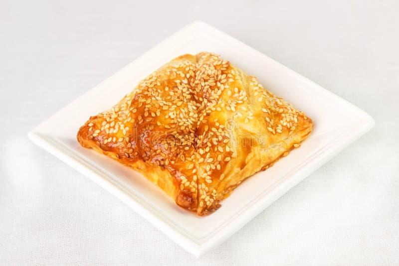 Gelaagde zoete broodjes in sesam op driehoekige plaat op witte backgr royalty-vrije stock fotografie