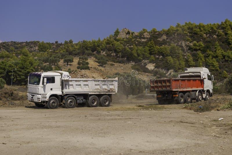 Geladen moderne stortplaatsvrachtwagens die bouwgrond van de bouwwerf vervoeren royalty-vrije stock foto