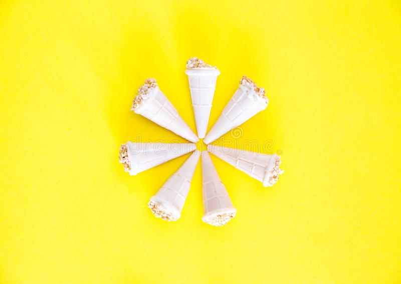 Gelado com as porcas em uns copos do waffle Os chifres da bolacha são arranjados sob a forma de uma flor em um fundo amarelo, clo fotos de stock royalty free