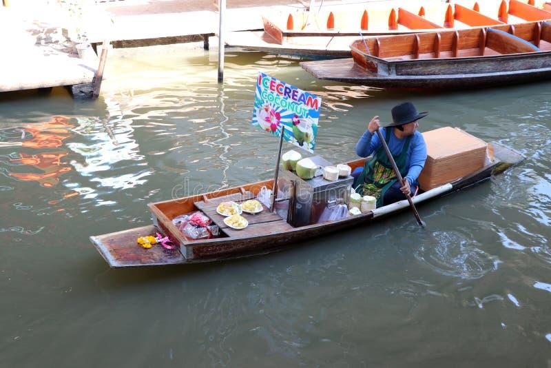Gelado com o vendedor do coco que senta-se em seu barco no canal no mercado de flutuação de Damnoen Saduak imagens de stock royalty free