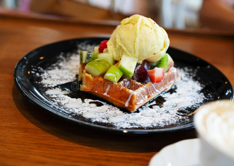 Gelado de baunilha com bagas, morangos, mirtilos, framboesas, maçã no waffle com açúcar pulverizado Conceito do alimento do verão imagens de stock