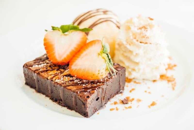 Gelado de baunilha com o bolo da brownie do chocolate com morango sobre imagem de stock royalty free