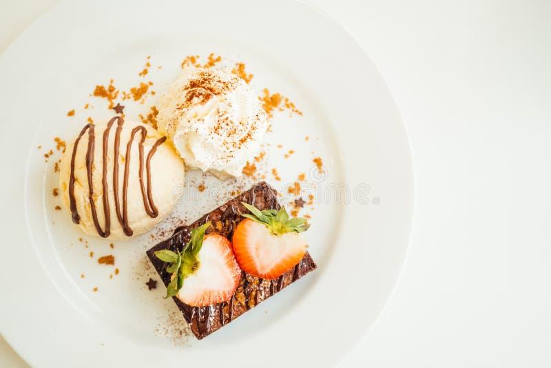 Gelado de baunilha com o bolo da brownie do chocolate com morango sobre fotografia de stock