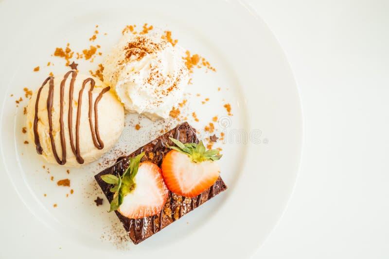 Gelado de baunilha com o bolo da brownie do chocolate com morango sobre imagens de stock