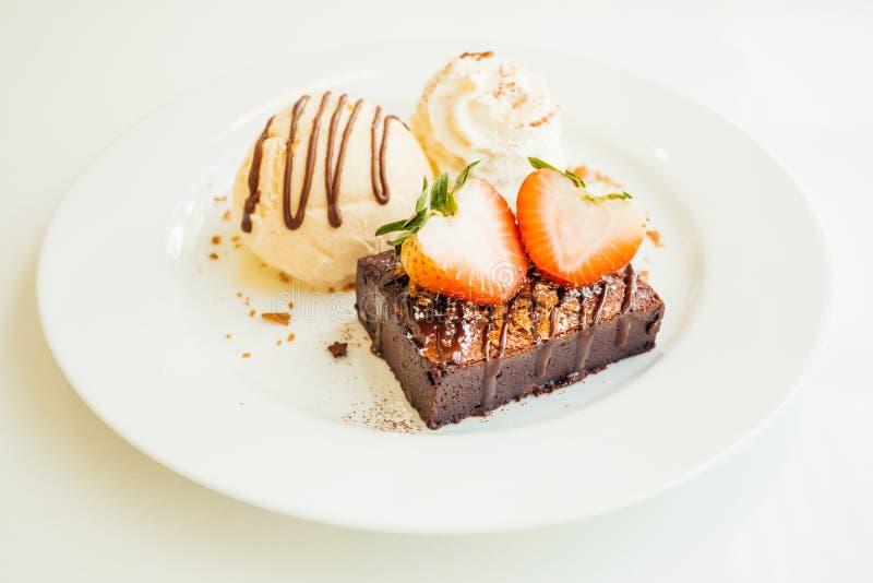 Gelado de baunilha com o bolo da brownie do chocolate com morango sobre foto de stock