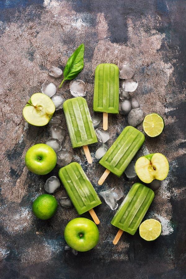 Gelado verde do fruto em uma vara Picolés verde-maçã Configuração lisa, vista superior imagem de stock