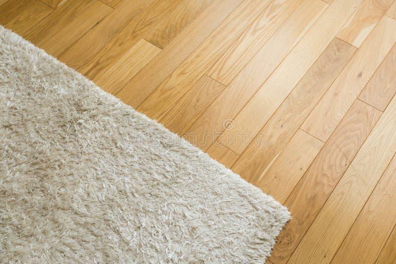 Gelamineerde parquetevloer Lichte houten textuur Beige zacht tapijt royalty-vrije stock fotografie