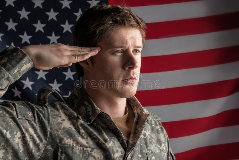 Gelassener Soldat, der einen Gruß steht und zurückbringt lizenzfreies stockfoto
