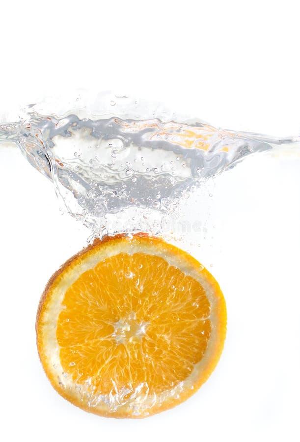 Gelaten vallen sinaasappel in geïsoleerd water stock foto's