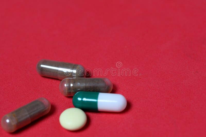 Gelatin pigułki i pastylki różni kolory Medycyny rozpraszać na tle koralowy kolor zdjęcia royalty free